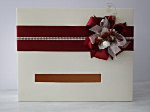 Кутия за пожелания Букет - Бордо Цена - 30.00 лв. Изработена от перлен екрю картон, декорирана със сатен, органза, рози и перли. Размер - 35x28x14 см.