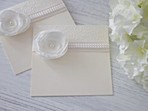 Покана Аида- екрю Цена - 2.50 лв. Кокетна сватбена покана, изработена от перлан картон, декорирана с красиво ръчно изработено цвете и перли. Размер сгъната 14x14 см.