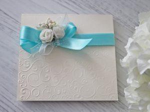 Покана Букет -квадратна, аквамарин 2.80 лв. Изработена от луксозен перлен картон, декорирана с релеф, сатенена панделка и рози. Размер сгъната - 14x14 см.