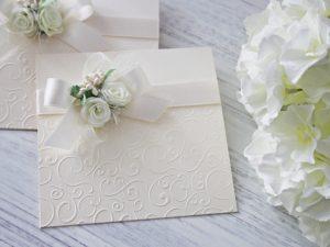Покана Букет -квадратна, екрю Цена - 2.80 лв. Изработена от луксозен перлен картон, декорирана с релеф, сатенена панделка и рози. Размер сгъната - 14x14 см.