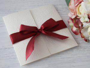 Покана Романс - бордо Цена - 2.30 лв. Изработена от луксозен перлен картон, декорирана с релеф, сатенена панделка. Размер сгъната - 14x14 см.