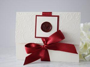 Покана Скарлет Сватбена покана с восъчен печат, който ще придаде лукс, аристократичност и класа. Покана е изработена от луксозен перлен картон в цвят екрю. Предната горна част е декорирана с релефни мотиви и сатенена панделка в цвят бордо, с помоща на която поканата се затваря.