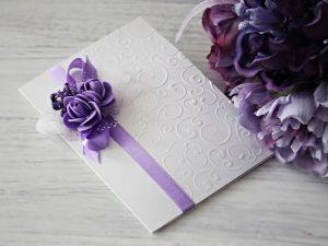 Покана Букет - Лилаво Цена - 2.80 лв. Изработена от луксозен перлен картон, декорирана с релеф, сатенена панделка и рози. Размер сгъната - 15x11 см.