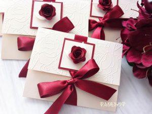 Покана Роуз. Ръчно изработена покана с триизмерен ефект. Покана е изработена от луксозен перлен картон в цвят екрю. Предната горна част е декорирана с релефни мотиви и сатенена панделка в цвят бордо, с помоща на която поканата се затваря. Акцент в поканата е ръчно изработена роза в съответстващ на панделката цвят.