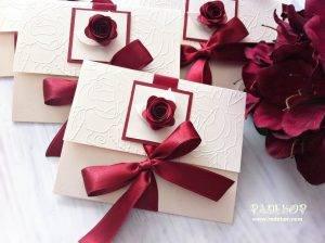 Покана РоузРъчно изработена покана с триизмерен ефект. Покана е изработена от луксозен перлен картон в цвят екрю. Предната горна част е декорирана с релефни мотиви и сатенена панделка в цвят бордо, с помоща на която поканата се затваря. Акцент в поканата е ръчно изработена роза в съответстващ на панделката цвят.