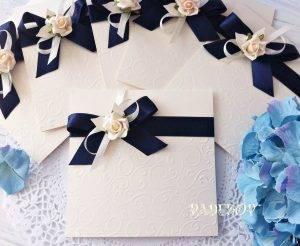 Покана Дивна - тъмно синьо Романтична сватбена покана, изработена в квадратна форма от луксозен перлен картон в цвят екрю. Предната част е декорирана с нежни релефни форми. Завършена е с красива сатенена панделка и малка силиконова роза в кремав цвят.