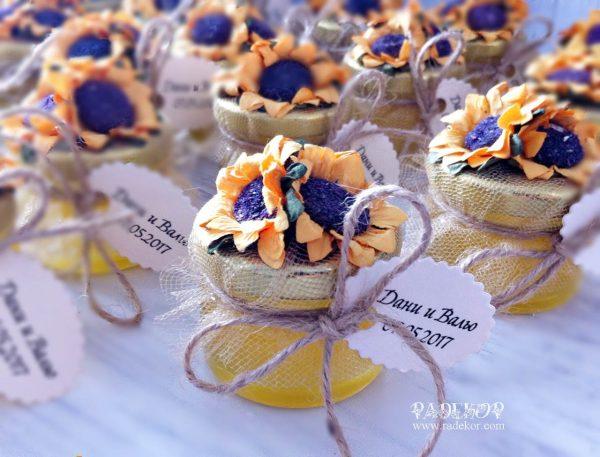 Подарък за гости Мед. Украсено мини бурканче с мед, подарък за спомен на гостите присъствали на тържеството. Декорацията е поставена върху капака на бурканчето и се състои от кристален тюл, канап и три слънчогледа.
