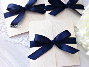 Покана Романс - тъмно синьо Поканата е изработена в квадратна форма от луксозен перлен бял. Предните части са декорирани с релеф от рози, сатенена лента обгръща цялата покана, и е оформена в красива панделка, в тъмно син цвят.
