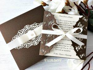Покана Магнолия. Дантелена сватбена покана, допълнена с кутия. Подходяща да бъде поднесена, като специална покана за кумове и родители. Поканата е с квадратна форма е се състои от две части. Външната част е тип обложка с красиво изрязана ажурна дантела, в шоколадово кафяво и завързана със сатенена панделка.