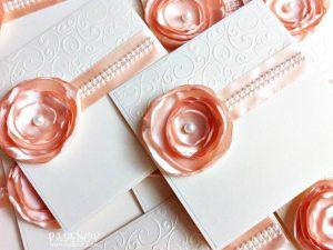 Покана Аида - прасковено Кокетна сватбена покана, изработена от перлен картон в цвят екрю, декорирана с релефи акцентирана с красиво ръчно изработено цвете в прасковен цвят