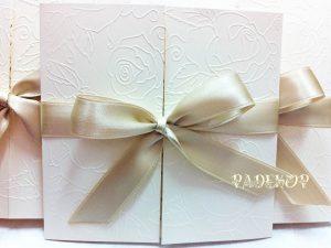 Покана Романс - карамел Ръчно изработена покана за сватбав квадратна форма от луксозен перлен екрю картон. Предните части са декорирани с релеф от рози, сатенена лента обгръща цялата покана, и е оформена в красива панделка, в цвят карамел.