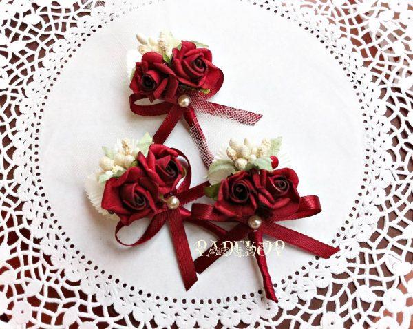 Бутониера Букет - бордо Сватбена бутониера, тип брошка за закичване на ревер. за гостите на сватбата. Състои се от две малки силиконови рози, с допълваща украса в цвят бордо. За по лесно поставяне в задната част има безопасна игла. Минимално количество за поръчка - 5 бр.