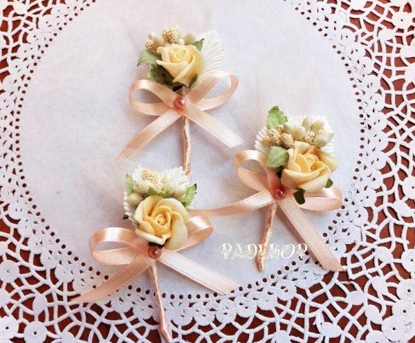 Бутониера Дивна - прасковено Бутониера за закичване на ревер Ръчно изработена бутониера, за закичване на гостите на сватбата, Състои се от малка силиконова роза с допълващи елементи в екрю и прасновено. За по лесно поставяне в задната част има безопасна игла.