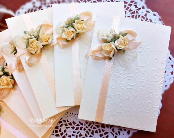 Покана Букет - прасковено Сватбени покани, изработени от луксозен перлен картон в цвят айвъри. Декорирани е с релеф, сатенена панделка в прасковено и завършени с букет от силиконови рози.