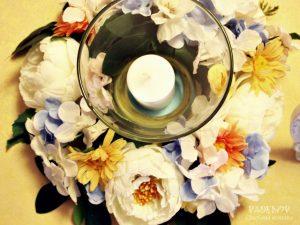 Цветна аранжировка от изкуствени цветя. Украса за маса за гости, подходяща за сватба и за кръщене. Венец от изкуствени цветя, поставен около стъклен свещник.
